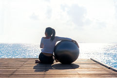 Healthy woman lifestyle balanced yoga ball practicing meditate and energy on the bridge in morning the seashore. Healthy Concept stock image