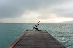 Healthy woman lifestyle balanced yoga practicing meditate and energy on the bridge in morning royalty free stock photo