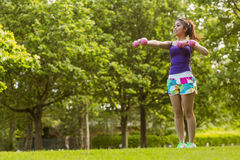 Healthy woman lifting dumbbells in park Stock Photography