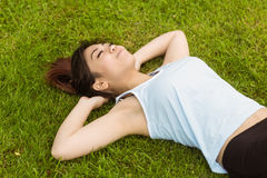 Healthy woman lying on grass in park Stock Photos
