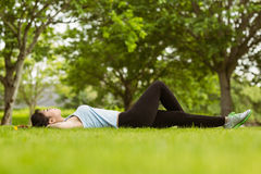 Healthy woman lying on grass in park Stock Photo