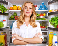 Healthy woman near open fridge Stock Images