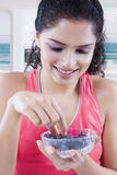 Healthy woman picks up blueberries on a bowl Royalty Free Stock Photos