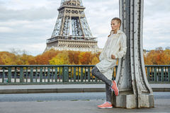 Healthy woman on Pont de Bir-Hakeim bridge looking into distance. Year round fit & hip in Paris. Full length portrait of young healthy woman on Pont de Bir Royalty Free Stock Photo