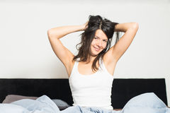 Healthy woman refreshed after a good nights sleep. Stretching in bed and smiling at the camera in pleasure and satisfaction royalty free stock image