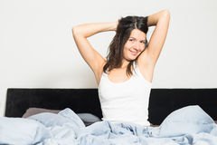 Healthy woman refreshed after a good nights sleep. Stretching in bed and smiling at the camera in pleasure and satisfaction Stock Photos