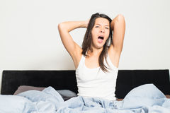 Healthy woman refreshed after a good nights sleep. Stretching in bed and smiling at the camera in pleasure and satisfaction stock photo