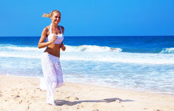 Healthy woman running on the beach. Doing sport outdoor, freedom, vacation, heath care concept with copy space over natural background Royalty Free Stock Photo