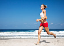Healthy woman running on the beach. Doing sport outdoor, freedom, vacation, heath care concept with copy space over natural blue background Stock Image