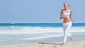 Healthy woman running on the beach. Girl doing sport outdoor, happy female exercising, freedom, vacation, fitness and heath care concept with copy space over Royalty Free Stock Images