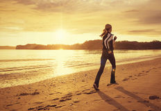 Healthy woman running on the beach at sunset. A rear view of a healthy woman running on the beach with a golden sunset in the background. Intentional lens flare Stock Images