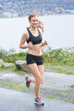 Healthy woman running near water outside Stock Photography