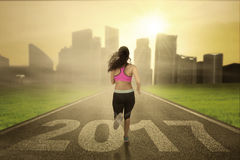 Healthy woman runs on road with 2017 Stock Image