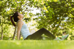 Healthy woman sitting on grass in park Royalty Free Stock Photo