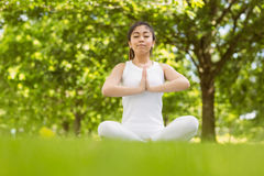 Healthy woman sitting with joined hands at park Royalty Free Stock Image