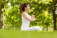 Healthy woman sitting with joined hands at park Royalty Free Stock Photography