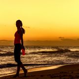 Healthy woman in sportswear on beach with bottle of water Stock Photography