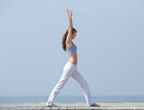 Healthy woman stretching body at the beach Stock Images