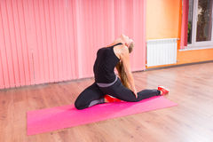 Healthy Woman Stretching her Back inside a Studio Stock Images