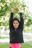 Healthy woman stretching her hands during exercise at park Stock Image