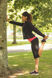 Healthy woman stretching her leg during exercise at park Royalty Free Stock Images