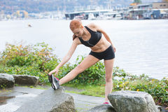 Healthy woman stretching before an outdoor run Royalty Free Stock Images