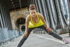 Healthy woman stretching on Pont de Bir-Hakeim bridge in Paris Royalty Free Stock Images
