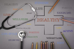 HEALTHY word cloud, health cross concept. Colored pencils and a. Stetoscope on the table Royalty Free Stock Photos