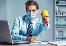 Healthy worker at the office holding lemon. Photo of man wearing protective mask against infectious diseases and flu. Business and health care concept stock images