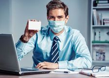 Healthy worker at the office holding white box of medicine. Photo of man wearing protective mask against infectious diseases and flu. Business and health care royalty free stock photos