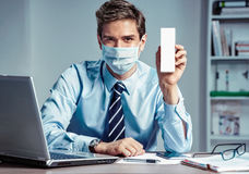 Healthy worker at the office holding white box or medicine. Royalty Free Stock Photography
