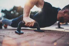 Healthy workout lifestyle concept.Training outdoors.Handsome sport athlete man doing pushups in the park on the sunny royalty free stock image