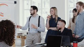 Healthy workplace concept, young businessman leading group discussion at modern office team meeting slow motion RED EPIC. Multiethnic smiling business stock video