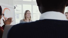 Healthy workplace. Diverse business people clap to young blonde CEO business woman at team meeting slow motion RED EPIC.
