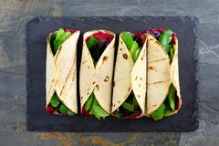 Healthy wraps with beet hummus, avocado and spinach, above view on slate. Healthy vegan wraps with beet hummus, avocado and spinach. Above view on a dark slate stock photo