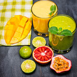 Healthy yellow and  green smoothies with tropical fruits Stock Image