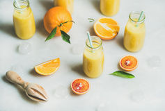 Healthy yellow smoothie with citrus fruit, marble background. Healthy yellow smoothie with citrus fruit, ginger, ice in glass bottles over light marble table Stock Photo