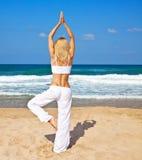 Healthy yoga exercise on the beach stock photography