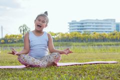 Healthy yoga girls and concentrate in the park , kid Yoga Practice for Health in the nice day , yoga kid stock images