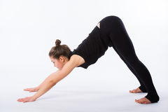 Healthy yoga stretching woman does a downward facing dog. This is part of a series of various yoga poses by this model stock photo