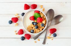 Healthy yogurt with berries and granola, top view over a bright background Stock Photos