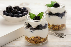 Healthy yogurt dessert with muesli, blackberries and  blueberries on white wooden table. Stock Photo