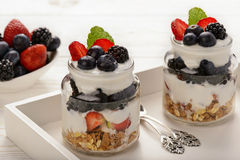 Healthy yogurt dessert with muesli, strawberries, blackberries and  blueberries on white wooden table. Stock Image