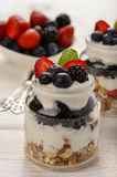 Healthy yogurt dessert with muesli, strawberries, blackberries and  blueberries on white wooden table. Royalty Free Stock Image