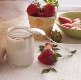 Healthy  yogurt and fresh strawberry berries. On the table Stock Image