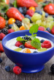 Healthy yogurt. Plain yogurt with mixed fresh fruit in a blue ceramic bowl Royalty Free Stock Image