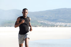 Healthy young african man running along the seashore Royalty Free Stock Images