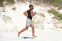 Healthy young african man running barefoot on the beach. Full length side portrait of healthy young african man running barefoot on the beach Stock Image