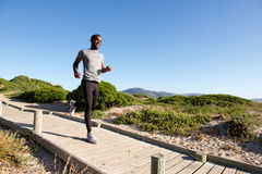 Healthy young african man running on boardwalk at the beach Stock Photos