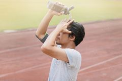 Healthy young Asian fitness man splashing water on his face after run in track of stadium. Sunshine effect. Healthy young Asian fitness man splashing water on Stock Image